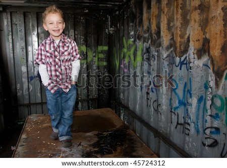 Little boy in a small shed with graffiti - stock photo