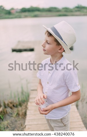 little boy in a white straw hat on the river with wooden bridge - stock photo