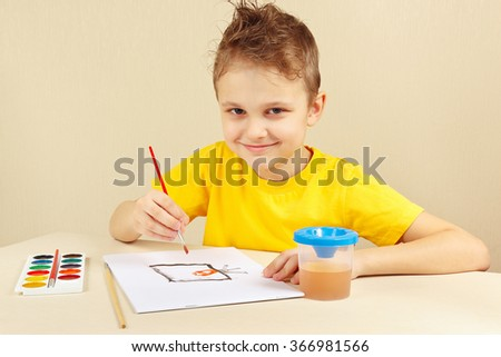 Little boy in a yellow shirt painting with watercolors - stock photo