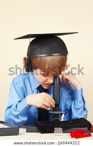 Little boy in academic hat studying something in a microscope - stock photo