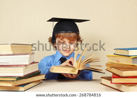 Little boy in academic hat turns the pages of an old book - stock photo