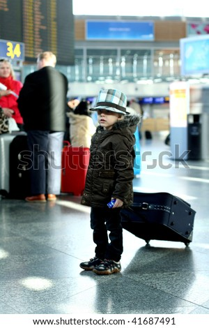 Little boy in airport with luggage - stock photo