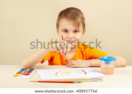 Little boy in an orange shirt painting with watercolors - stock photo
