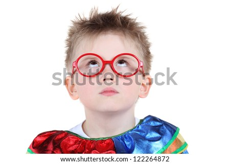 Little boy in big red glasses and clown costume looks up isolated on white background. - stock photo