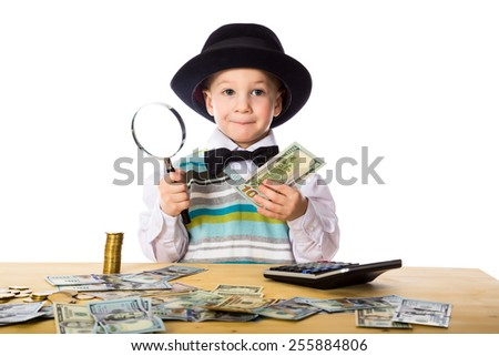 Little boy in black hat counting money on the table, isolated on white - stock photo