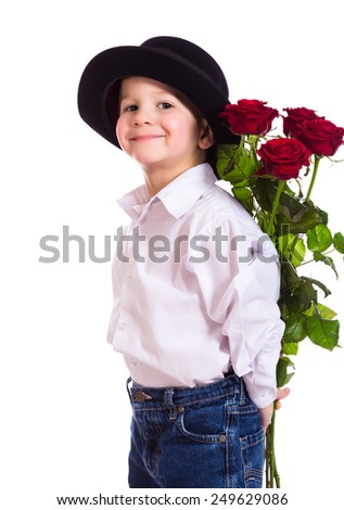 Little boy in black hat hide the bouquet of red roses, isolated on white