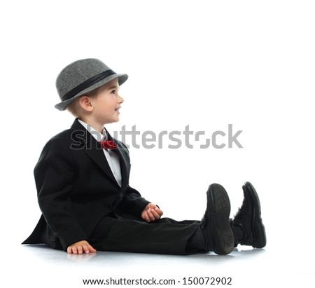 Little boy in black suit  and grey hat sitting on a floor - stock photo