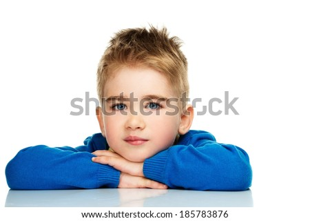 Little boy in blue cardigan and yellow shirt behind table - stock photo
