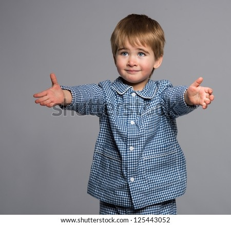 Little boy in blue pyjamas with arms wide open - stock photo