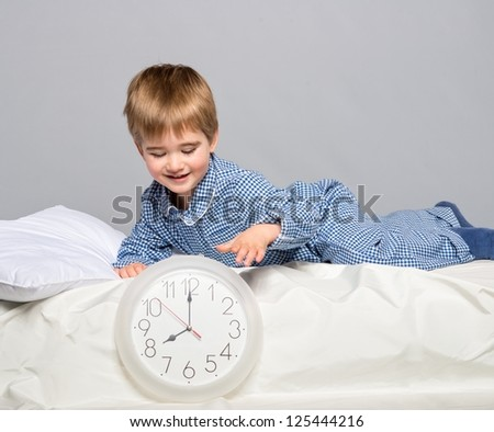 Little boy in blue pyjamas with clock - stock photo