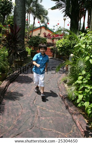 Little boy in blue shirt running in the garden on a sunny day - stock photo