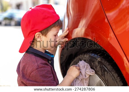 Little boy in cap cleaning red car wheel, outdoor - stock photo