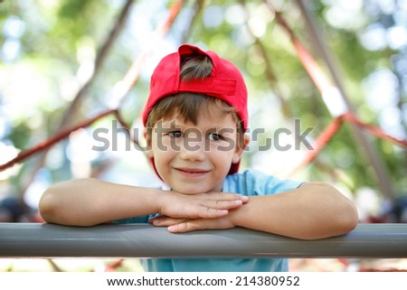 Little boy in cap on the jungle gym, looking away