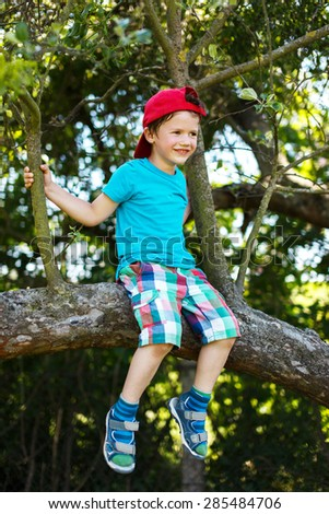 Little boy in cap sitting up a tree on summer - stock photo