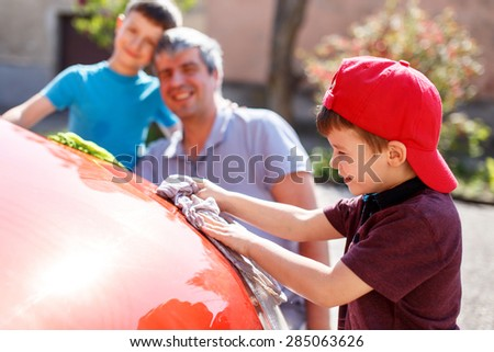 Little boy in cap washing car with dad and brother, fun with family - stock photo
