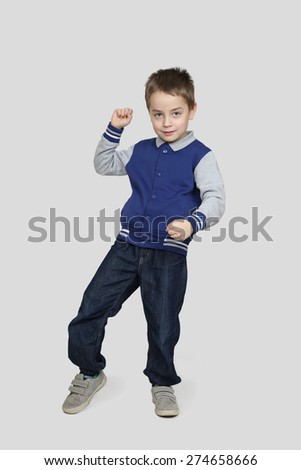 Little boy in casual clothes dances on gray background - stock photo