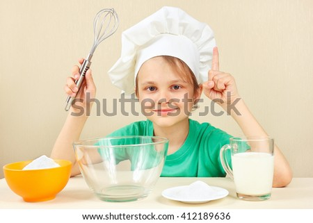 Little boy in chef hat at the table with ingredients is going to cook a cake - stock photo