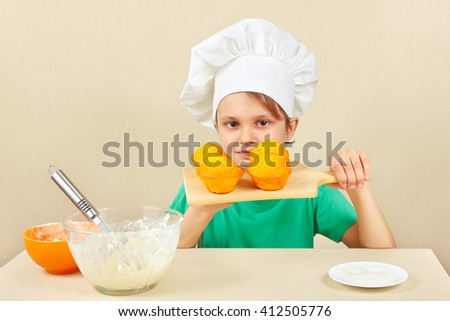 Little boy in chef hat with a cooked the appetizing cake - stock photo