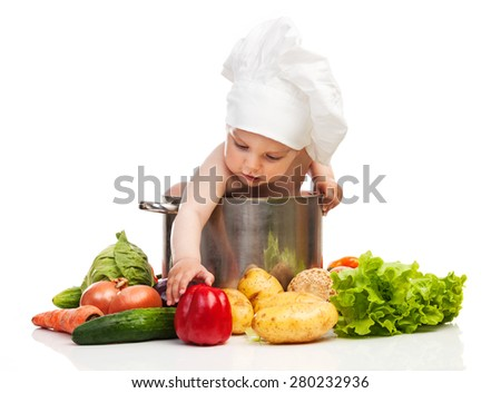 Little boy in chef's hat reaching for bell pepper while sitting in large casserole over white - stock photo