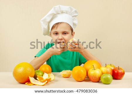 Little boy in chefs hat eat fresh orange at the table with fruits