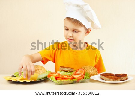 Little boy in chefs hat puts cheese on the hamburger - stock photo