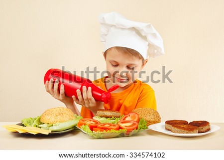 Little boy in chefs hat puts ketchup on the hamburger - stock photo