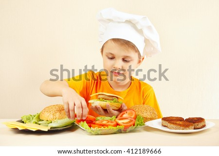 Little boy in chefs hat puts tomato on the hamburger - stock photo