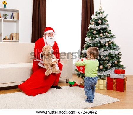 Little boy in Christmas, Santa Claus showing toy from bag - stock photo