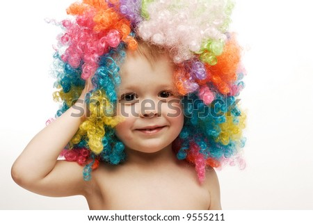 Little boy in colorful bright wig holding his head laughing looking straight - stock photo