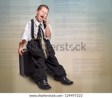 Little boy in daddy business suit sitting in briefcase - stock photo