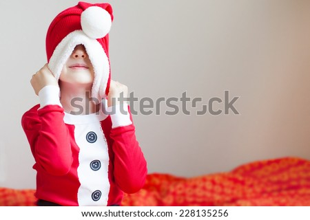 little boy in elf costume pulling hat down and being silly at christmas time at home - stock photo