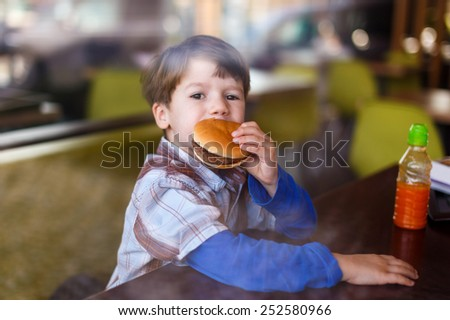 Little boy in fast food restaurant eat hamburger behind glass - stock photo