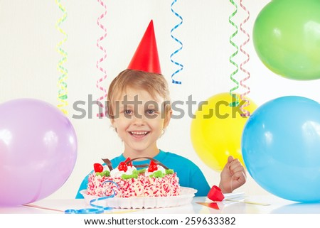 Little boy in festive hat with a birthday cake and balloons