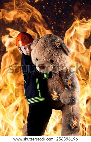 little boy in firefighter uniform save the teddy from the flames - stock photo