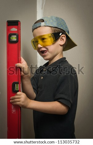 Little boy in goggles with a wall level - stock photo