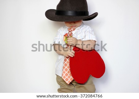 Little boy in hat and tie holding a red paper heart, lowering his gaze and looking confusedly, isolated portrait on white background, romantic and love concept - stock photo