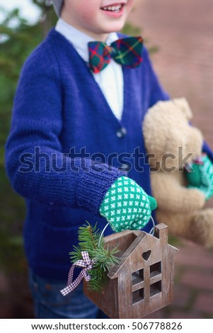 little boy in knitted sweater and mittens holding in hands handmade wooden house candle holder and teddy bear outdoors. sweet cozy winter time. winter wonderland. winter still life. christmas card