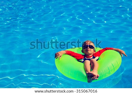 little boy in life ring having fun on summer beach  - stock photo