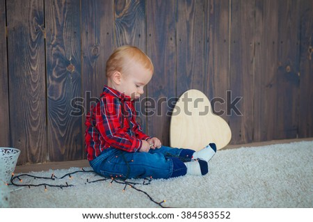 Little boy in red shirt playing on the floor. Boy 1 year.