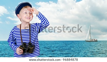 Little boy in sailor's uniform with binoculars looks into the distance from the arm at the sea view