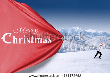 Little boy in santa hat is pulling christmas banner - stock photo
