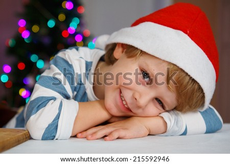 Little boy in santa hat with christmas tree and lights on background - stock photo