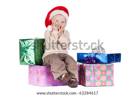 little boy in santa hat with gifts - stock photo