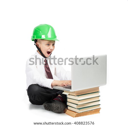 Little Boy in school suit and helmet sitting with laptop computer and books. White Background isolated - stock photo