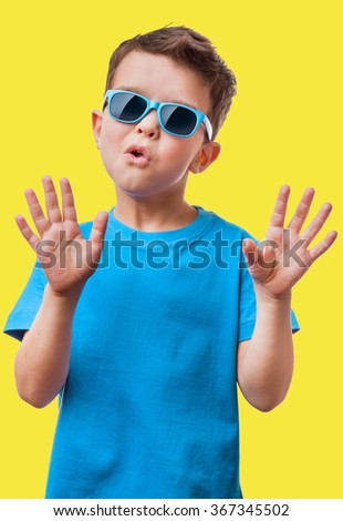 Little boy in sunglasses raised his hands up, on yellow background
