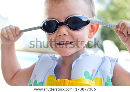Little boy in swimming goggles and an inflated plastic buoyancy jacket on a hot summer day as he prepares to go swimming in the pool - stock photo
