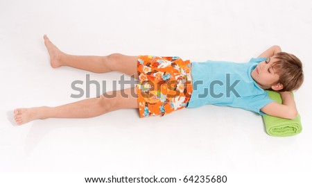 Little boy in swimming trunks lying with his head on a rolled up beach towel - stock photo