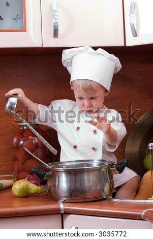 little boy in the cook costume at the kitchen sitting on the table