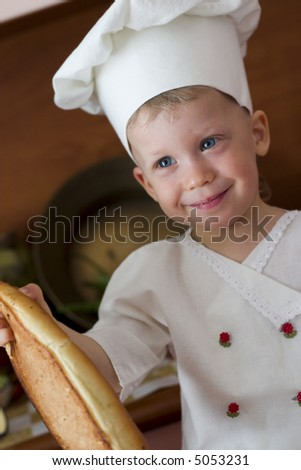 little boy in the cook costume at the kitchen sitting on the table - stock photo
