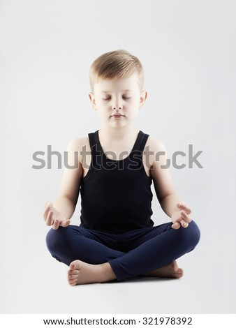 little boy in the lotus position.child does yoga.meditation and relaxation for health - stock photo